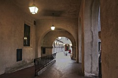 Hallway Museum of Man (iseedre) Tags: hallway courtyard walkway stucco railings lights winter evening pavers arches windowstableandchairs woman redcoat umbrella