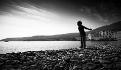 Ricochet (elgunto) Tags: beach stones cadaqués kid play ricochet sea sky clouds movement wideangle blackwhite bw nikon2035 sonya7 manuallense ai