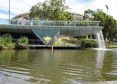 Adelaide. The glass footbridge  from the Adelaide Railway Station across the Torrens River to the Adelaide Oval. (denisbin) Tags: adelade bridge footbridge torrensriver adelaideoval fountain conventioncentre
