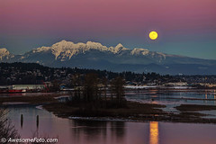Sunset glow and moonrise (james c. (vancouver bc)) Tags: winter canada mountain snow canadian white scenic outdoor summit travel evening tourism beautiful peak nature landscape reflection hill tree leafless goldenearsmountain britishcolumbia scenery serene sunlight log sky red sunset river plant water factory storage industry building industrial residential cargocontainer islet ripple pink dusk moonrise moon supermoon fullmoon glow afterglow orange