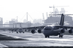 London City Airport, UK. (Greg Bajor) Tags: city uk greatbritain travel england bw london monochrome lines plane airplane fly flying blackwhite moving airport traffic unitedkingdom britain aircraft altitude aviation air united jets airplanes great transport flight jet kingdom aeroplane business commercial queue depart transportation airline planes commuter docklands british concept airways airports conceptual gregory airlines bae departure propeller takeoff runway lufthansa flights regional airliner londoncityairport airliners aerospace bae146 flaps fokker taxiing 146 silvertown birdlike lcy bajor aviationart eglc gregbajor