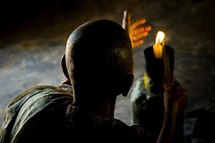Buddhist monk praying in Angkor, Cambodia (Eric Lafforgue) Tags: light temple fire asia camb