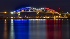 sault ste. marie international bridge, michigan (twurdemann) Tags: longexposure railroad bridge summer colour reflection water night unitedstates michigan upperpeninsula redwhiteandblue tricolour saultstemarie frenchflag soolocks internationalbridge movablebridge stmarysriver basculebridge verticalliftbridge ledlighting nikcolorefex 16x9crop tonalcontrast camelbacktruss internationalrailroadbridge reflectorefex xf55200mm fujixt1