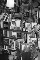 Buried among books (Images by Arden) Tags: urban blackandwhite bw blancoynegro monochrome boston book store fuji noiretblanc massachusetts streetphotography newengland highcontrast bookstore fujifilm salesman allston shopkeeper siyahbeyaz xe1 blancoenero imagesbyarden fujifilmxe1 fujifilmxseries
