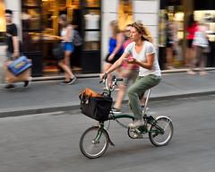 Hold the phone . . . (jeremyhughes) Tags: d750 nikon urban city folder foldingbike mobile mobilephone street woman cyclist cycling bicycle bike brompton phone rome panning motion movement speed