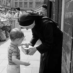 Little boy putting money in nun's collection tray (National Library of Ireland on The Commons) Tags: elinorwiltshire rolleiflexcamera rolleiflex wiltshirephotographiccollection elinorobrienwiltshire reginaldwiltshire wiltshire rip nun boy charity moorestreet dublin littlesistersofthepoor market favourites potatoes inmemoriam