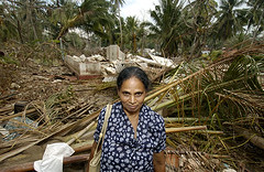 A woman in front of the remains of her tsunami-destroyed home