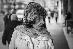 Diverted Attention (Leanne Boulton) Tags: closeup urban street candid portrait portraiture profile streetphotography candidstreetphotography candidportrait streetportrait streetlife old elderly woman female face facial expression look emotion feeling eyes nose fur hat winter clothing tone texture detail depthoffield bokeh bokehlicious naturallight outdoor light shade city scene human life living humanity people society culture canon canon5d 5dmkiii 70mm character ef2470mmf28liiusm black white blackwhite bw mono blackandwhite monochrome glasgow scotland uk