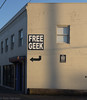 Free Geek! (Wolfy) Tags: portrait usa white signs black building sign wall architecture oregon word portland concrete outdoors daylight us spring symbol unitedstatesofamerica gray commercial electronics northamerica arrow ontheground lettering insignia lightandshadow magichour communications goldenhour greys exteriors businesssign directionalsign exteriorview cinderblockwall verticalorientation identificationsign