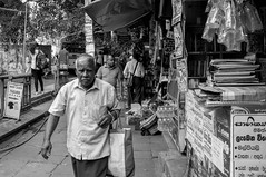 Streets of Kandy (Aadil Chouji Schiffer) Tags: street streetphotography streets photography kandy srilanka ceylon asia south east country asian people human humans fuji fujix100 x100 rangefinder miroless bw bnw bandw blackandwhite blacknwhite blackwhite black white mono monochrome market shop shops shacks roadside vendors