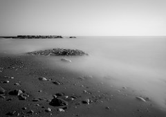 The Beach (R*Wozniak) Tags: longexposure wisconsin water minimalism blackwhite bw blackandwhite nikon slowshutter sand rocks beach a6000 sony 16mm