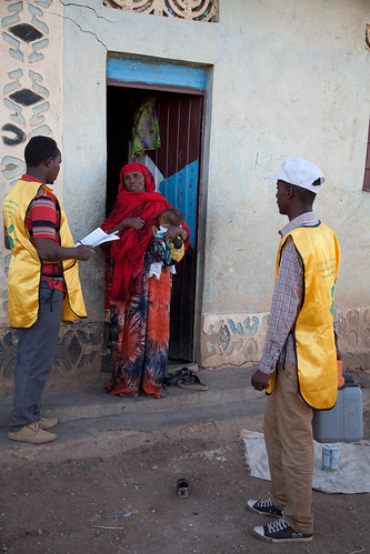 Sophia Ege Bulale carries her three month old grandson Hamad Mukhtar Dayib, while discussing with the team of vaccinators that have come to her home