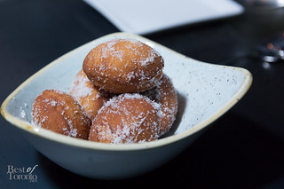 Bomboloni, raspberry-filled fritters with vanilla sugar coating.