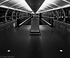 Terminal Tubes (B&W version) (Greg Adams Photography) Tags: terminal monochrome bw blackandwhite manchester england greatbritain uk unitedkingdom travel people silhouettes silhouette lights windows airport vanishingpoint walkway walking europe eu 2016 fall