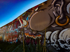 A Blowhard (Steve Taylor (Photography)) Tags: art graffiti mural streetart wall colourful spooky eerie scary man newzealand nz southisland canterbury christchurch city perspective spring sky blowhard blowing skull earring