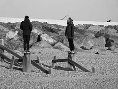 Guard Duty... (cngphotographic) Tags: man woman female monochrome blackandwhite beach shoreline shingle outside outdoors outdoor broomhillsands camber eastsussex fujifilm hs50exr opensource rawtherapee linux couple sunshine winter england britain wooden posts rocks seawall defences cold hats finepix pebbles sands uk