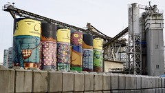 Os Gemeos' 'Giants' lighting up the cement plant on Granville Island (planted city) Tags: vancouver city westcoast bc beautiful britishcolumbia canada winter life granvilleisland osgemeos giants art cities publicart design streetart mural industry cement architecture