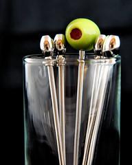 Macro Mondays - Redux 2016 - DSC03487P2 (Scott Glenn) Tags: shotglass cocktailpick stainlesssteel olive silver green red blackbackground closeup macro sonysal70300g 4filter macromondays notliketheothers redux2016myfavoritethemeoftheyear