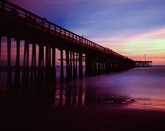 Ghosts on the Pier (Blurmageddon) Tags: film analogphotography slidefilm fujichrome velvia100 expiredfilm 4x5 graflex speedgraphic venturacalifornia pier sunset longexposure epsonv700