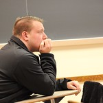 A student intently listening to a presentation given by one of his fellow classmates.