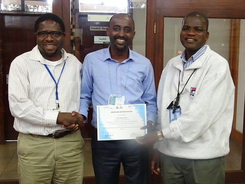 Appolinaire Djikeng, BecA-ILRI Hub Director (left) and Wellington Ekaya Senior Scientist, Capacity Building (right) present Prof Gobena Ameni with his certificate of participation