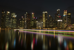 Colors in darkness (elenaleong) Tags: skyscraper reflections singapore cityscape nightlights citylights lighttrails touristattraction singaporeriver marinabay boattrails marinareservoir