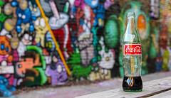 Coca Cola  (Explored) (KC Mike Day) Tags: coke coca cola drink half empty bottle glass alley grafitti bokeh color artalley crossroads art straw cup bench table picnic