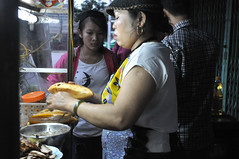 On a roll (Roving I) Tags: streetfood vendors vietnam breadrolls earrings women aprons busstations tourism travel hoian
