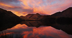 Moke Lake at Sunset - Queenstown - New Zealand (South Island) (Rogg4n) Tags: morning travel blue trees light sunset newzealand wild sky sun mist mountain lake reflection nature water colors misty fog clouds forest sunrise wonder landscape fire mirror spring quiet sony south country foggy symmetry clear nz southisland queenstown burningsky wilderness doc volcanic cristal wanaka brume limpid waterscape compactcamera mokelake nouvellezélande doccampsite dscwx300 sonydscwx300