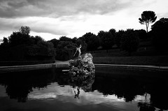 """Meeting Neptune"" (helmet13) Tags: leicaxvario bw italy florence thefountainofneptune boboligardens park sculpture pond silence woman visitor aoi heartaward peaceaward"