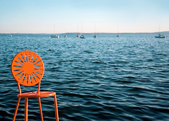 Memorial Union Sunburst Seat on Lake Mendota (Todd Klassy) Tags: chair orange lake mendota madison water sea memorial union boats sail horizon wi wisconsin outdoors stockphotography clearsky bluesky copyspace madisonwisconsin universityofwisconsin sunburstchair memorialunion terrace memorialunionterrace lakemendota cityofmadison travel tourism visit waves ripples bodyofwater madisonphotographer toddklassy madisondocumentaryphotographer uw badgers theunion shore shoreline boating recreation fun entertainment watersports outdoorspace patio deck student dining uwmadison campus seat colorful pattern sun school university backtoschool college education big10 bigten annex collegeunion selectivefocus buckybadger hoofers waterscape urbanscene city lakefront starburst inviting