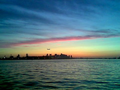 Boston from the water (bettlebrox) Tags: cameraphone pink sunset sky water boston clouds plane phonecam bay harbor 2000 harbour 2006 landing loganairport mick logan 1000 sunet bostonharbour bostonharbor nokia6020 boston2006 mickt bostonpres25