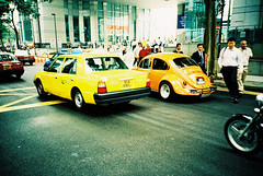 Volkswagen Beetle (GenkiGenki) Tags: road people orange film car yellow vw volkswagen lomo lca xpro crossprocessed singapore colorful fuji cab taxi beetle fujifilm backview rafflesplace sensia sensia400 32mm
