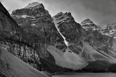 Towering Mountain Peaks Around Moraine Lake (Black & White, Banff National Park) (thor_mark ) Tags: nikond800e day4 triptoalbertaandbritishcolumbia banffnationalpark overcast valleyofthetenpeaks morainerockpiletrail morainelake lake lookingssw blackwhite silverefexpro2 capturenx2edited colorefexpro outside nature landscape mostlycloudy cloudsaroundmountains lowclouds rockymountains canadianrockies mountains mountainsindistance mountainsoffindistance mountainside trees evergreens hillsideoftrees glacialflour glaciallake glacialvalley morainelakearea valley fayglacier glacier snowcapped mountainvalley continentaldivide lookingtocontinentaldivide lookingtomountainsofthecontinentaldivide southerncontinentalranges banfflakelouisecorearea bowrange mountbabel mountlittle mountbowlen mounttonsa mountperren project365 portfolio alberta canada