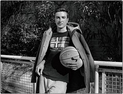 Federico (Steve Lundqvist) Tags: game sports play persone sport basket pallacanestro blackandwhite bw fujifilm x100s explore court light pov angle portrait ritratto young youth boy ragazzo sportswear moda fashion parka model casting models clothes ball pallone airstyle fence basketball monochrome posed pose mood athlete player training napapijri nba university mvp college