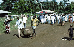 Sierra Leone 1979-80 A drum being carried along the road ahead of a crowd of people, announcing the arrival of a Paramount Chief at the Moslem New Year 31st Oct, Mange Village, N.Province (mani-media) Tags: people for book aerial sierra business infrastructure summit pr leone healthcare 197980 oau