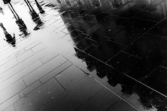 Rain (gambajo) Tags: street light people blackandwhite reflection wet water rain umbrella blackwhite floor streetphotography slope