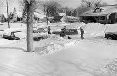 Men carry shovels, a woman carries fire logs near 2377 Elm Street in Denver, Colorado. (Denver Public Library Digital Collection)