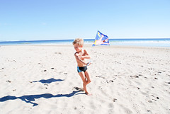 Child playing with a kite on the beach in november