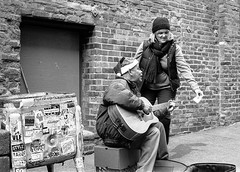 Guitar player, Post Alley (1 of 1) (sailronin) Tags: seattle postalley pikeplace film analog kodak5222 hc110h man guitar busker woman alley bricks hat bw leicamp 50mmsummicron