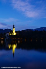 Dusk over Lake Bled (Ian Middleton: Photography) Tags: travel trees summer vacation lake holiday mountains alps reflection building history tourism church water beautiful architecture clouds religious island evening still scenery europe european dusk famous scenic eu tourist tourists architectural historic christian clear slovenia touristy stunning bled backdrop former christianity popular yugoslavia attraction shimmering eec slovenian slovene gorenjska slavic