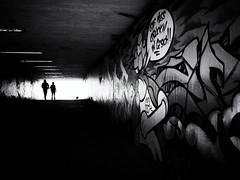 Through the underpass (Sandy...J) Tags: urban underpass tunnel grafitti noir darkness light blackwhite monochrom streetphotography silhouette walking