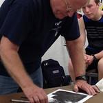 Students watch an artist demonstration during class.