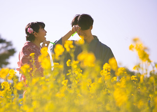 Happy young kimono couple in rape blossoms field