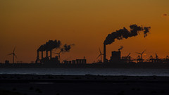 Electricity factories burning coal. And windmills for clean energy. (Guido Speekenbrink) Tags: energy backlight maasvlakte netherlands coal harbour industry twilight windmill smoke orange