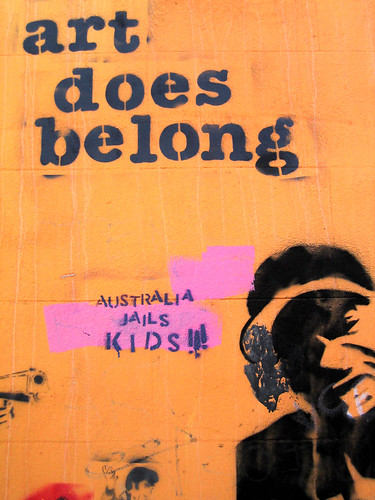 "graffiti: text ""art does belong"" and a stencil of a person's face and then the spray-painted words, ""australia jails kids"""