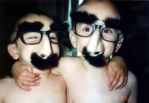 Two kids wearing big nose, glasses, and mustaches