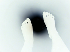 picture taken looking down at one's feet--the silhouette of two bare feet in white standing on top of a black hole