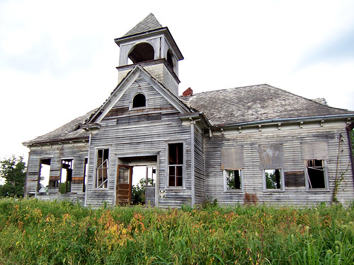 Abandoned wooden schoolhouse, so delapidated that the fields and woods behind it can be seen through the empty windows and door frames.