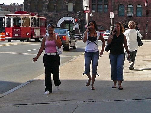 3 women walking together while on cell phones